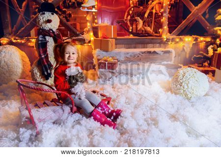 Pretty three year old girl sits on the sled in the yard of her house and holds snow in her hands.Time for miracles. Merry Christmas and Happy New Year.