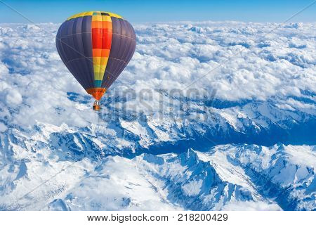 Aerial view from colorful hot air balloon flying over mountains with snow and clouds.