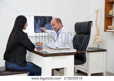 Doctor explaining female patirnt that she has curvature of the spine