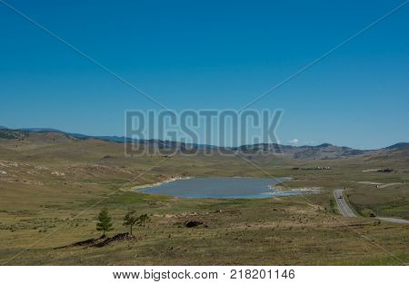 Landscape with rural asphalt road through the steppe, clouds on blue sky summer day. Beautiful landscape. Road landscape. Road. Adventure