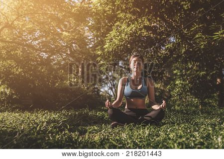 Yoga in the park outdoor with effect light health woman Yoga woman. Concept of healthy lifestyle and relaxation. vintage tone. yoga in park. girl yoga relex. yoga fitness. yoga concept.