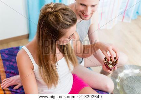 Young man gives his girlfriend chocolate candy for Valentines day as a sign for his love