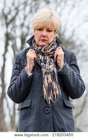 Depressed or sad woman walking in winter garden