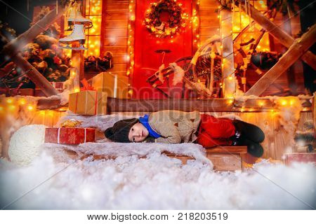 Cute child boy lies on the porch near his house decorated for Christmas. Time for miracles. Merry Christmas and Happy New Year.