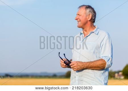 Senior man looking away with joy and hope while daydreaming outdoors in the countryside in a sunny day