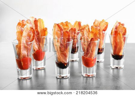Glasses with cooked bacon rashers and sauces on table