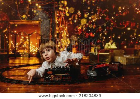 Cute five-year-old boy playing with a toy railway near the Christmas tree. Christmas night. Christmas decoration.