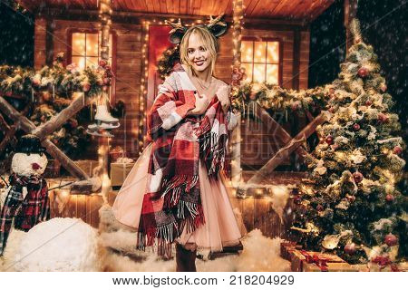 Happy girl in a beautiful dress, wrapped in a blanket, stands near the house decorated for Christmas. Time for miracles. Merry Christmas and Happy New Year.