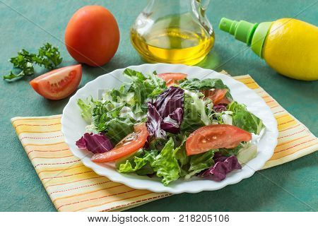 Ingredients for preparation of vitamin salad: different salad leaves tomatoes olive oil lemon with spray pump. Healthy food and vitamins