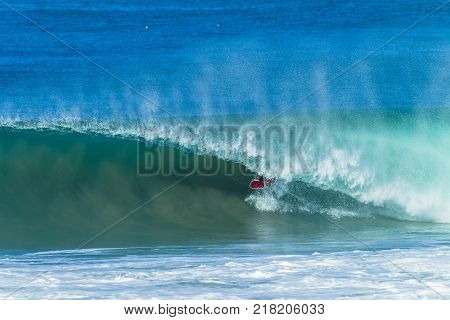 Surfing surfer unidentified tube rides inside hollow ocean wave overlooking action photo.