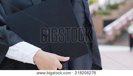 Woman wearing graduation gown and holding mortarboard