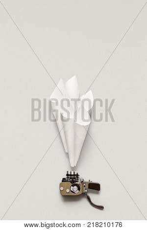 Creative concept photo of old vintage camera with paper on grey background.