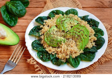 Avocado quinoa salad. Easy quinoa salad with fresh spinach leaves and avocado slices on a served plate. Brown wooden background. Rustic style. Closeup