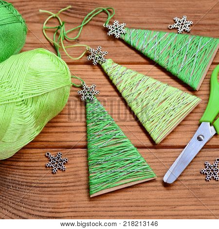 Little Christmas trees are made of carton, cotton yarn and decorated with small metal snowflakes. Easy and cheap Christmas crafts for kids can make. Affordable Christmas crafts