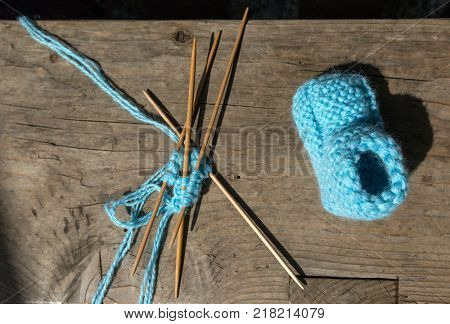 knitting of socks of blue wool, knitting needles on a wooden table