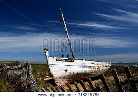 Olhao,Rias Formosa,Portugal - APRIL 28: an old wooden fishing boat, called Marselhesa,  aground on the Beach Rias Formosa,  . April 28, 2015 in Olhao,Rias Formosa,Portugal.