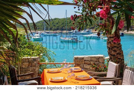 Yachts on anchor in Milne Bay photographed from the terrace of a restaurant - Hvar, Croatia