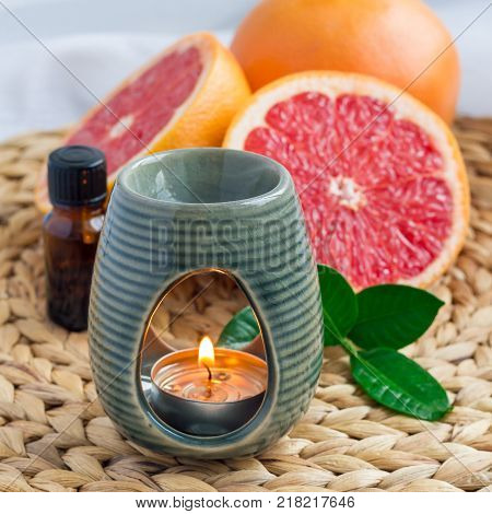 Aroma lamp with grapefruit essential oil on woven mat grapefruits on background square