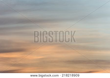 Defocused sunset sky background with a golden orange glow on a hazy clouds over twilight blue.