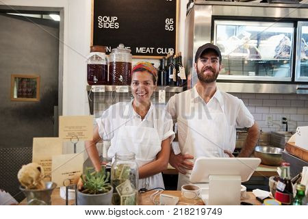 Man and woman ready to serve behind the counter at butcher's