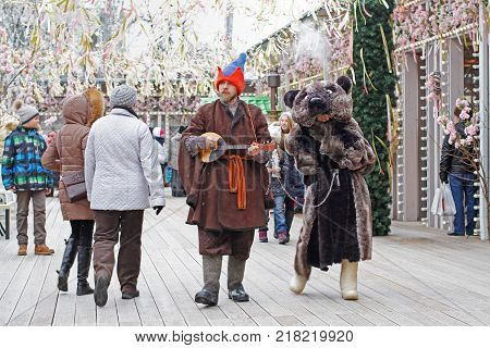 Moscow Russia - February 25 2017: Buffoon with balalaika and bear at Russian national festival