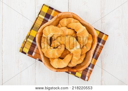 Wooden bowl with freshly baked homemade croissants on shabby chic background top view