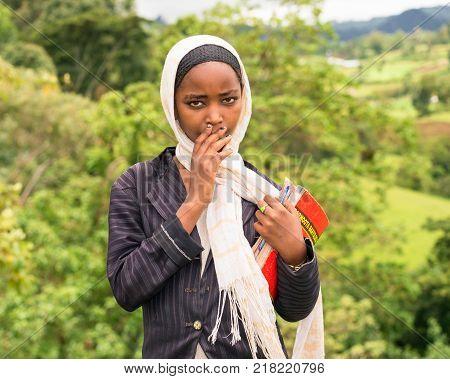 ADDIS ABABA, ETHIOPIA - MAY 4, 2015 : Young ethiopian schoolgirl carrying her exercise books.