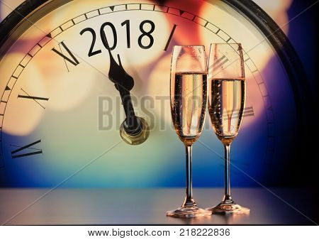 champagne glasses and gvintage clock showing 2018 ready to bring in the New Year