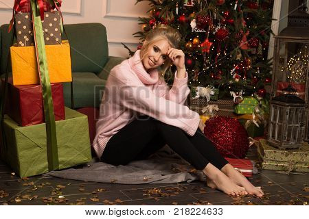Beautiful smiling young girl sit on the flour in her room with a big gift box and happy smiling while sit near Christmas Tree and look at the camera. Christmas decorate, New Year mood
