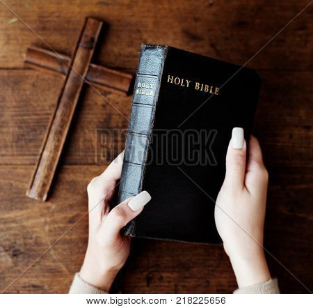 Female hands holding a bible and a wooden cross