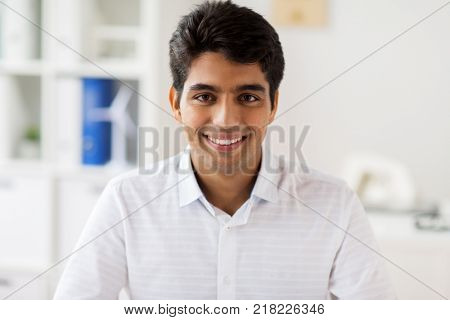 business and people concept - smiling indian businessman at office