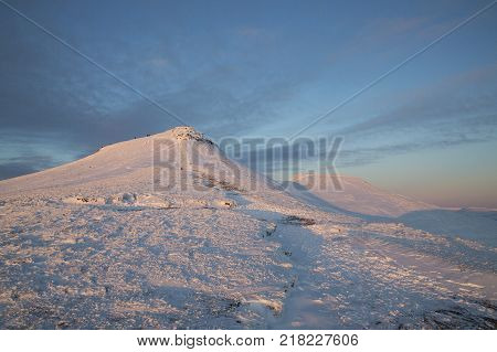 Winter snow scene at dusk on Pen y Fan mountain in the Brecon Beacons National Park, UK. A popular location for serious walkers and hikers.