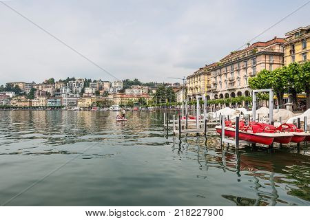 Lugano Switzerland - May 28 2016: View of embankment of Lugano Lake. Lake Lugano (Lago di Lugano) is nestled between Lake Maggiore and Lake Como and lies partly in Switzerland and partly in Italy.