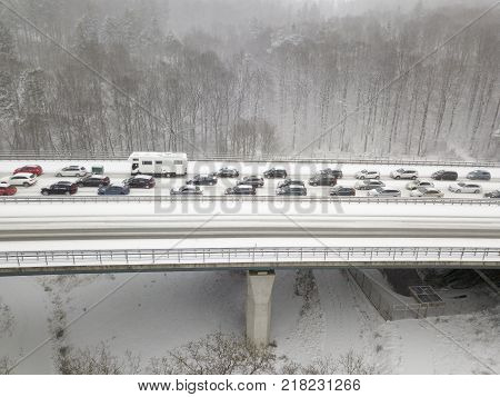 Cars on a highway bridge during a heavy snowfall in winter