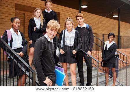 Portrait Of Teenage Students In Uniform Outside School Building
