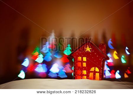 Beautiful Christmas decor, tiny red decorative house over glowing lights background, festive colorful lights in Christmas trees shape, happy winter holidays