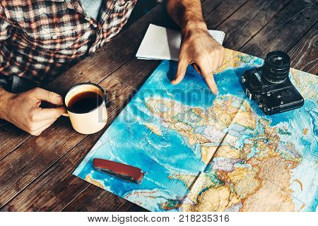 Man's hand indicates a route on a paper map. Another hand holds a mug of tea. The man is inspired by photography and plans a hike on a dark wooden table