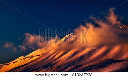 Beautiful sunset over snowy mountains, landscape of Cedar mountains, big mountain covered with snow in bright yellow sunset light, amazing nature of Lebanon