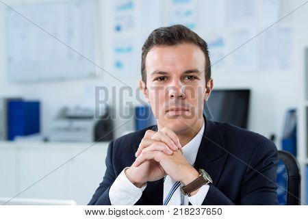 Portrait of unsmiling handsome businessman looking at camera