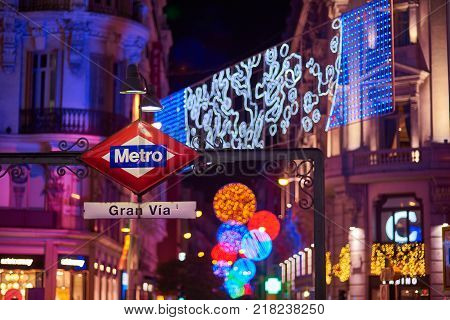 Madrid, Spain - December 12, 2017. Gran Via metro station signboard at night with Gran Via and Hortaleza streets illuminated by christmas lights, located in central Madrid. View from Montera street.