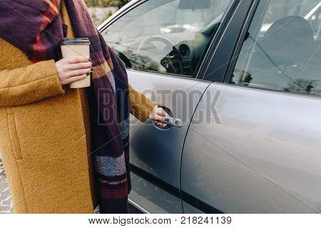 partial view of woman holding car door handle