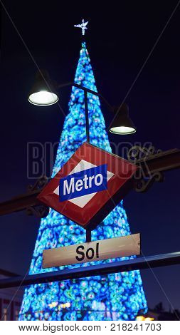 Madrid, Spain - December 12, 2017. Puerta del Sol metro station signboard at night with a shinny christmas tree in background.