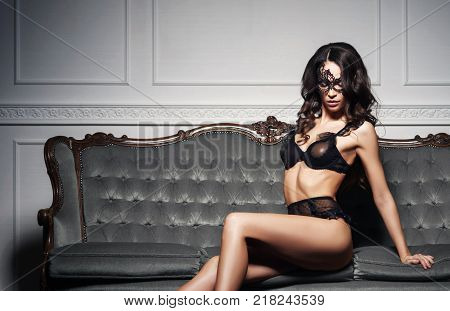 Beautiful and young woman posing in sexy lingerie and Venetian mask on grey sofa. Vintage interior and retro background.