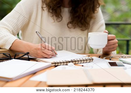 Cropped image of female university student drinking coffee and writing an essay in outdoor cafe