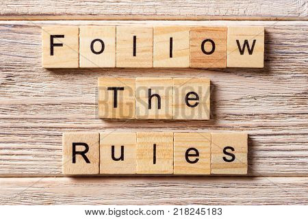 Follow The Rules word written on wood block. Follow The Rules text on table concept.