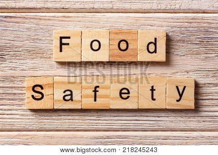 Food safety word written on wood block. Food safety text on table concept.