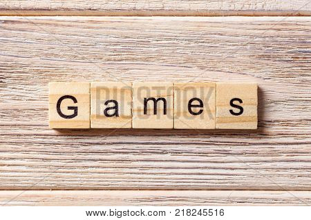 games word written on wood block. games text on table concept.