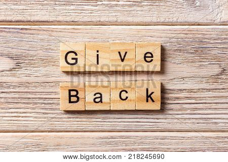 Give Back word written on wood block. Give Back text on table concept.