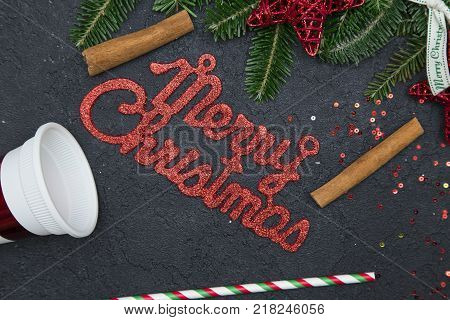 Red gleaming Merry Christmas inscription with traditional ornaments on a black concrete background. Close up. Top view poster