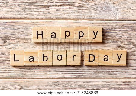 Happy Labor Day word written on wood block. Happy Labor Day text on table concept.